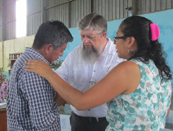 Jim Kerwin and Lilian de Chávez praying with a pastor in Bethania